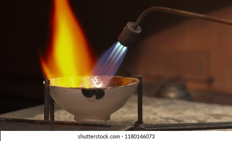 Professional jeweler using gas torch for melting precious metal. Close up of handlers tilting crucible to the sides. Jewelry specialist directing the flame right on the sterling silver