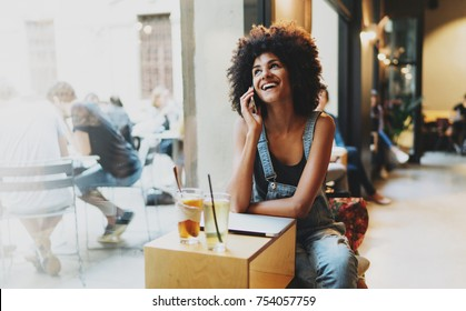 Professional journalist glad to receive answer by a mobile phone call that her article is accepted for the next newspaper edition. Beautiful mixed race woman using a laptop and smartphone.