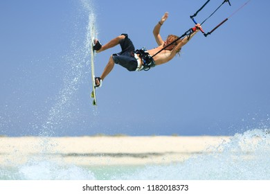 Professional kite boarding rider sportsman with kite in sky jumps high acrobatics kiteboarding trick with grab of kiteboard and huge water splash. Recreational activity, extreme active air sports