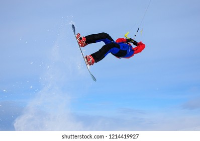 Professional kite boarding rider sportsman with kite in sky jumps high acrobatics kiteboarding trick with grab of kiteboard. Recreational activity, extreme active sports, snowkiting ski snowboard