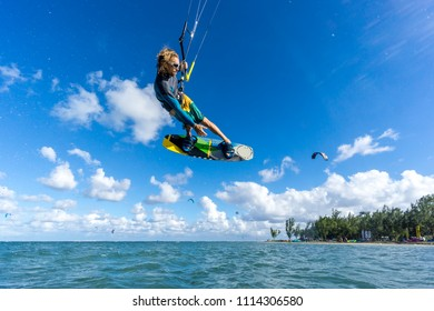 professional kiter makes the difficult trick on a beautiful background of spray and beautiful clouds of Mauritius