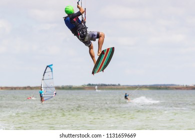 professional kiter makes the difficult trick on a beautiful background of spray