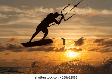 professional kiter makes the difficult trick on a beautiful background of spray and beautiful sunset of Mauritius