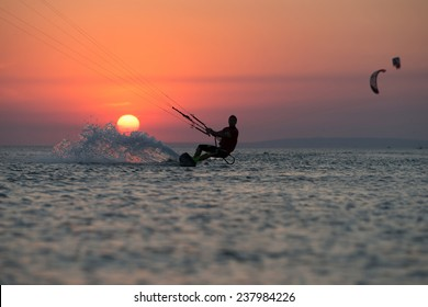 professional kiter rides on a beautiful background of spray and colourful sunset of Black sea