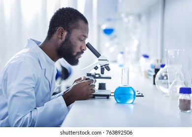 Professional laboratory. Smart handsome male scientist sitting at the table and looking into the microscope while working in the laboratory