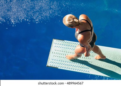 Professional lady diver preparing to dive from the spring board