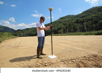 Professional land surveyor measures ground control point on a road construction site using GNSS rover on a pole