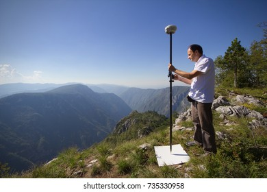 Professional land surveyor measures ground control point using a GNSS rover, while standing on a mountain cliff edge