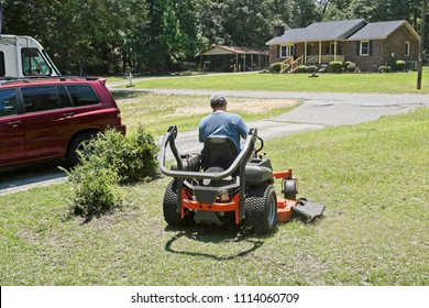 Professional landscaper cutting grass in a residential neighborhood with a zero turn lawnmower