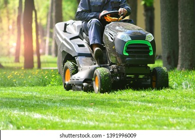 Professional lawn mower with worker cutting the grass in a garden - Shutterstock ID 1391996009