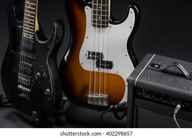 Professional level of playing musical intruments is needed to handle with this two beautiful guitars connected to an amp. Photo shoot in a studio.