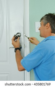 A professional locksmith is installing or repairing a new deadbolt lock on a house exterior door with the inside internal parts visible.