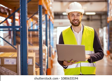 Professional logistics manager. Cheerful nice man smiling while dealing with logistics system in the storehouse