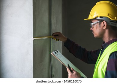 A professional look construction worker or inspector checking structure of building by using measuring tool and checklist.