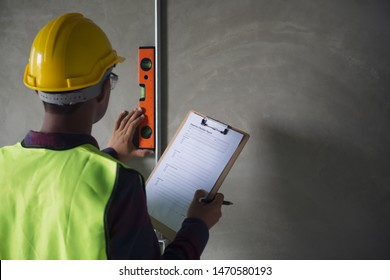A professional look construction worker or inspector checking detail of construction building by using level  measuring tool and checklist.
