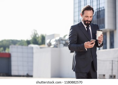 Professional look.Cheerful handsome businessman going to make a call while drinking coffee