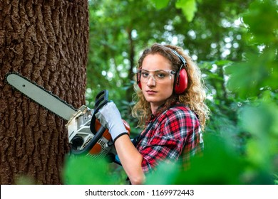 Professional lumberjack holding chainsaw by an oak tree in the forest. Female woodcutter with safety equipment for eyes and ears protection. Woman doing man's job. Gender equality.
