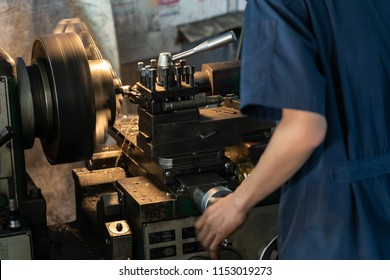 Professional machinist : man operating lathe grinding machine - metalworking industry concept. Mechanical Engineering control lathe machine in factory.