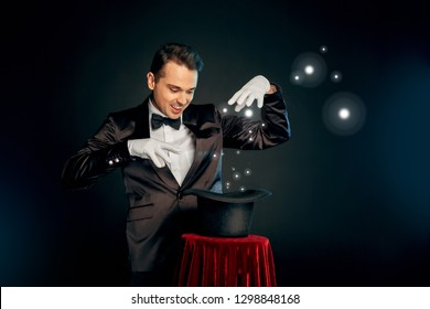 Professional magician wearing suit and gloves standing isolated on black and red background making trick with top hat on table smiling playful