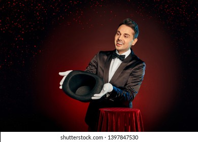 Professional magician wearing suit and gloves standing isolated on black and red background making trick showing empty top hat to audience smiling friendly