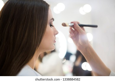 Professional make up artist doing make up in beauty salon. Close up