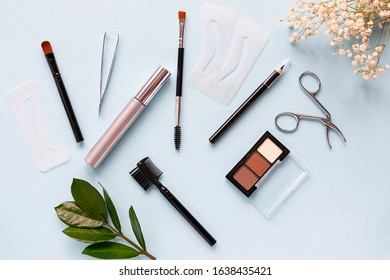 Professional make up set for eyebrows and eyelashes styling on light blue background. Beauty and fashion concept.