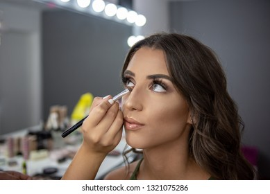 Professional makeup artist applies eye shadow with brush around eye of the model girl. Beautiful woman face with hands of make-up artist, makeup in progress