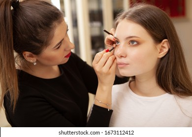 Professional makeup artist applying eye makeup on her female client