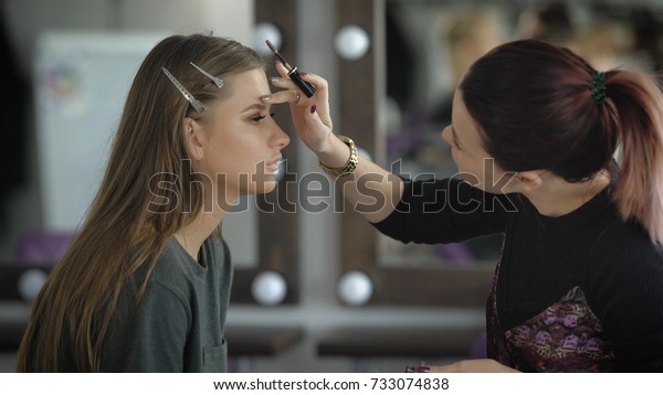 Professional makeup artist applying makeup master. Woman with hair tucked away in the tail emphasized gel for eyebrows brown eyebrows, giving the shape of eyebrows model