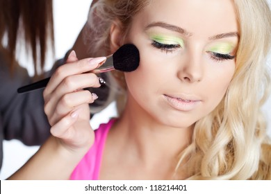 Professional makeup artist applying makeup on the face of the model
