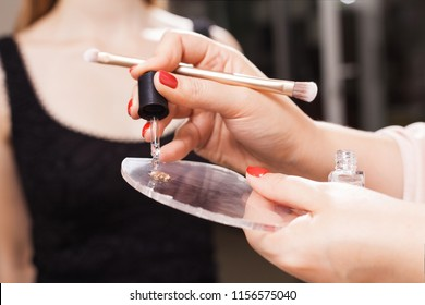 professional makeup artist mixing foundation and oil on a glassy surface before applying it on a face of a model. concept of natural make up