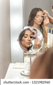 Professional makeup artist prepares  beautiful, young model for celebration, gala event, romantic dinner, party, photo shooting ... in front of the mirror in beauty studio