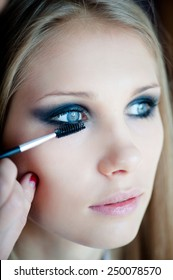 Professional make-up artist prepares a model for a photo shoot