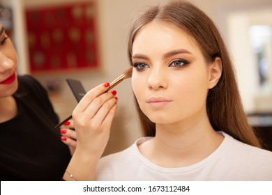 Professional makeup artist preparing model for fashion show, applying highlighter