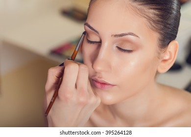 Professional make-up artist preparing model for studio shot.