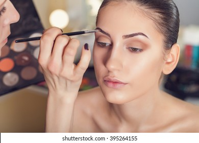 Professional make-up artist preparing model for studio shot.