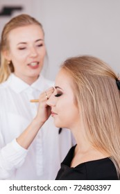 Professional makeup artist working with beautiful young woman in black dress