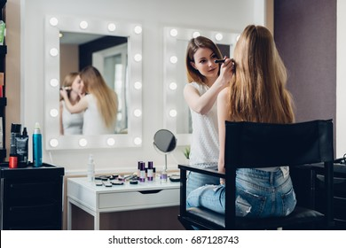 Professional makeup artist working on young girl creating natural look in beauty salon