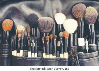 Professional makeup brushes cosmetic in tube, leather bag. close-up brush, makeup tools of , powder, set of different objects for makeup artist in their holder. Set of make up products arranged