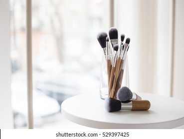 Professional makeup brushes in a glass