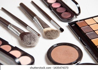 Professional makeup brushes for the highlighter of the foundation for make-up of the rouge blush coloring on a gray textured background
