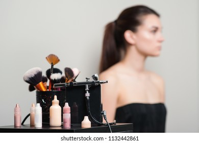 Professional makeup brushes, modern airbrush and tools. Make-up products set. Make up application tools. Cosmetics and brushes on on artist workplace.