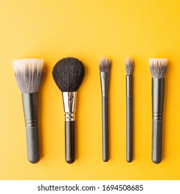 Professional makeup brushes top view on a yellow background with place for text. Skin care. Flatlay.
