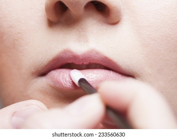 Professional makeup female beauty. Closeup girl young woman applying lipgloss lipstick on pink lips. Part of face.