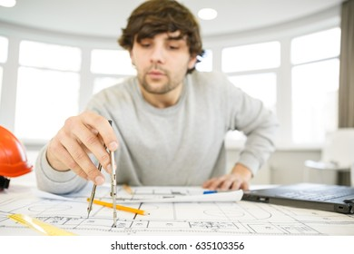 Professional male architect working at his desk drawing building plans using compass profession occupation job designer engineer construction development urbanization sketching business people