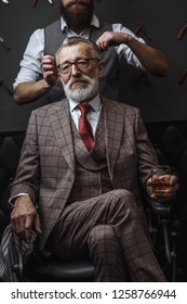 Professional male barber cutting hair of grey- haired wealthy man in years, dressed in fashionable three-piece suite. Process of creation of new hairdo in a luxury barbershop.