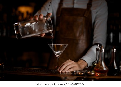 Professional male bartender pouring an alcoholic drink from the measuring cup to the martini glass on the bar counter in the dark blurred background