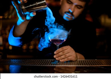 Professional male bartender pouring a smoke into the cocktail glass from the steel shaker under the blue light on the bar counter in the dark blurred background.