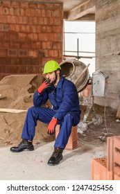Professional male contractor not doing his job, smoking on his duty with  construction clothes and protective equipment.