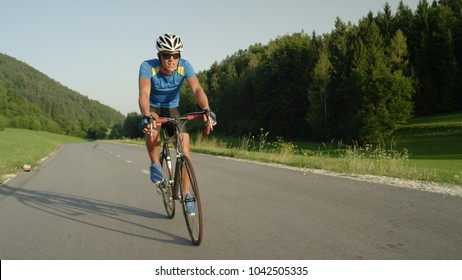 Professional male cyclist cruises down empty asphalt road on a sunny spring day in green nature. Active sportsman on a relaxing ride through the countryside. Young man riding his road bike in summer.